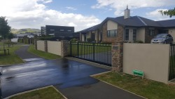 Elite wall with stone pillars and sliding gate